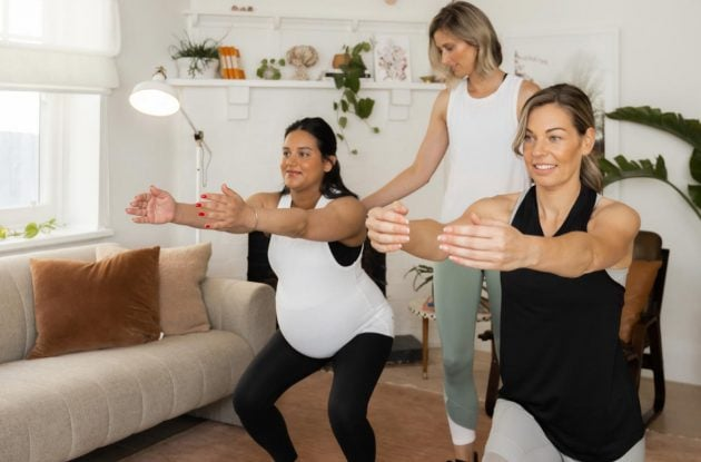 Kath instructing a pregnant mum and postnatal mum through a pilates workout