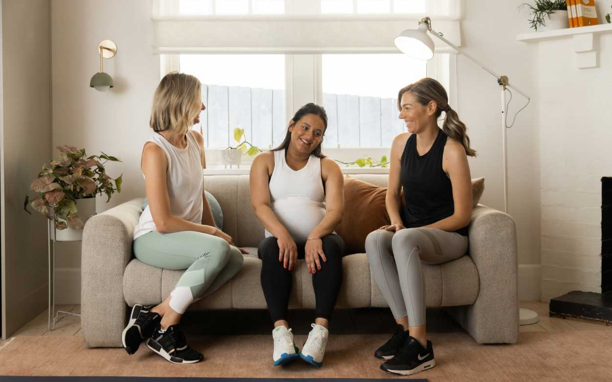 Kath sitting on couch in activewear with pregnant mum and postnatal mum